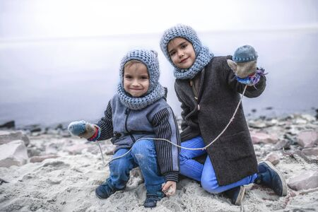 Little pretty girl in knitted grey hat sharing a pair of gloves with her frozen smaller brother during snowfall in winter, white cold weather, outside lifestyle portrait