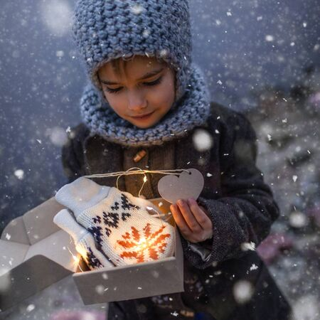 Little pretty girl in knitted grey hat opening a crafted gift box with a new pair of gloves. Baby, it is cold outside, white snowfall and cold weather, outside lifestyle portrait Banque d'images - 135492451