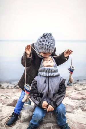 Little pretty girl in knitted grey hat proposes to share a pair of gloves with her frozen smaller brother during snowfall in winter, white cold weather, outside lifestyle portrait Banque d'images - 135492453