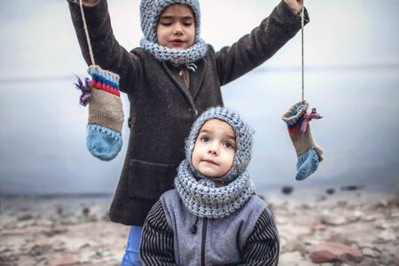 Little pretty girl in knitted grey hat proposes to share a pair of gloves with her frozen smaller brother during snowfall in winter, white cold weather, outside lifestyle portrait Banque d'images - 135491748