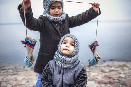 Little pretty girl in knitted grey hat proposes to share a pair of gloves with her frozen smaller brother during snowfall in winter, white cold weather, outside lifestyle portrait Banque d'images - 135491750