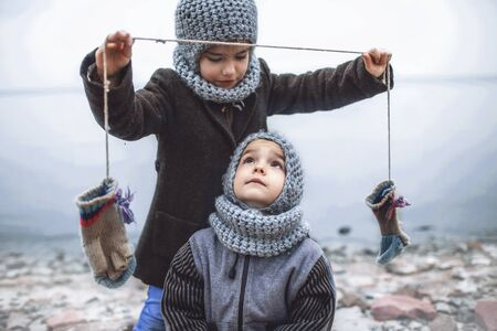 Little pretty girl in knitted grey hat proposes to share a pair of gloves with her frozen smaller brother during snowfall in winter, white cold weather, outside lifestyle portrait Banque d'images - 135491751