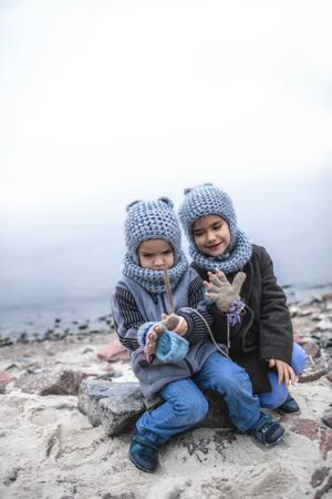 Little pretty girl in knitted grey hat sharing a pair of gloves with her frozen smaller brother during snowfall in winter, white cold weather, outside lifestyle portrait Banque d'images - 135491752