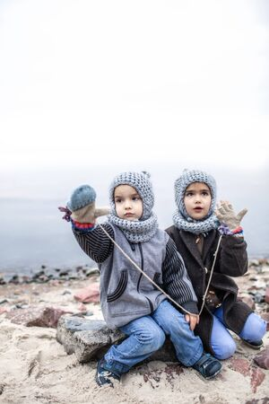 Little pretty girl in knitted grey hat sharing a pair of gloves with her frozen smaller brother during snowfall in winter, white cold weather, outside lifestyle portrait Banque d'images - 135491759
