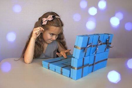 Cute little girl near a huge pile of blue gift boxes formed like a laptop over white studio background, she dreaming about laptop, season holiday wish concept Reklamní fotografie