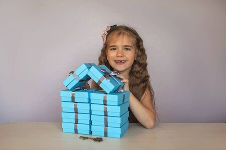 Cute little girl near a huge pile of blue gift boxes formed like a house over white studio background, she dreaming about new apartment, season holiday wish concept