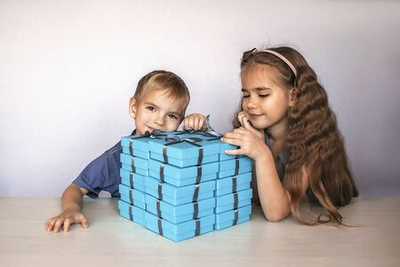 Cute little girl with her smaller brother near a huge pile of blue gift boxes with gray ribbons over white studio background