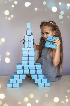 Cute little girl near a huge pile of blue gift boxes formed like Eiffel tower over white studio background, she dreaming about travel, season holiday wish concept