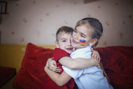 Cute young sport fans, boy and girl with colored cheeks, sitting on sofa, family watching sport games and cheering for her team on TV at home, real emotions, sports event and fun supporting concept 版權商用圖片