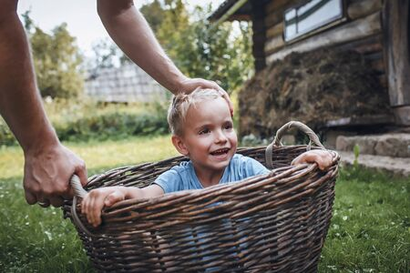 Cute little boy having fun together with his father and playing with hurdled basket on the backyard of old country house in village at summer, happy summertime in countryside, outside emotional lifestyle