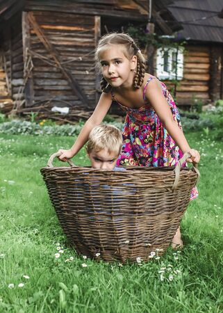 Cute little boy and girl having fun together and playing with hurdled basket on the backyard of old country house in village at summer, happy summertime in countryside, outside emotional lifestyle 版權商用圖片
