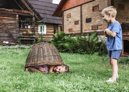 Cute little boy and girl having fun together and playing with hurdled basket on the backyard of old country house in village at summer, happy summertime in countryside, outside emotional lifestyle Stockfoto - 139198074