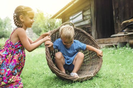 Cute little boy and girl having fun together and playing with hurdled basket on the backyard of old country house in village at summer, happy summertime in countryside, outside emotional lifestyle Stockfoto