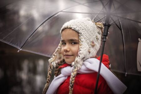 Happy pretty 7-8 years girl in red coat with transparent umbrella walking alone in early spring forest, emotional outdoor portrait
