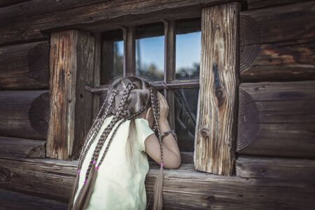 Adorable 7-8 years girl with many braids peering through an old wooden window of country house, happy summertime, countryside, emotional outdoor lifestyle Banco de Imagens