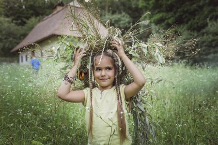 Adorable 7-8 years girl wearing beautiful wreath of summer flowers, golden wheat and green grass at the backyard of country house, happy summertime, countryside, emotional outdoor lifestyle
