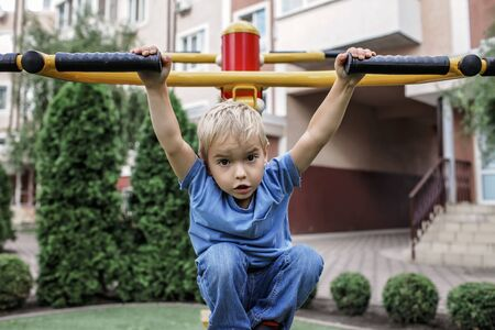 Handsome 4-5 years boy doing his exercises with device for sport at the playground outside in summer, physical activity and healthy lifestyle for everybody Imagens