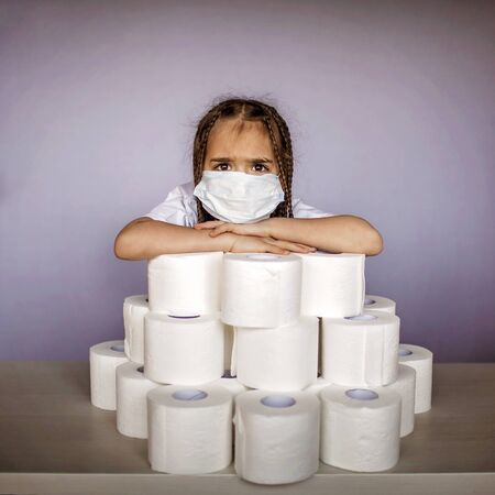 A cute girl wearing respirator mask sitting near the heap of toilet paper, basic thing in emergency coronavirus kit, prepare for self-isolation 版權商用圖片