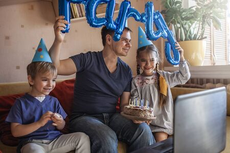 Happy father with two sibling celebrating birthday during internet party in quarantine time,  self-isolation and family values, online birthday party 版權商用圖片