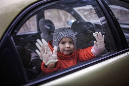 Little boy wearing respirator mask and medical gloves looking through a car window, stop travel, self-isolation during quarantine, stay safe concept