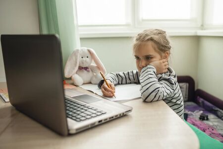 Pretty stylish schoolgirl studying homework math during her online lesson at home, social distance during quarantine, self-isolation, online education concept