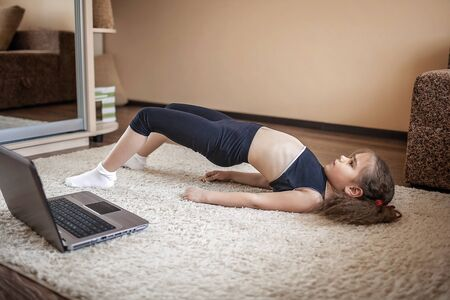 Pretty young girl in sportswear watching online video on laptop and doing fitness exercises at home. Distant training with personal trainer, social distance or self-isolation, online education concept