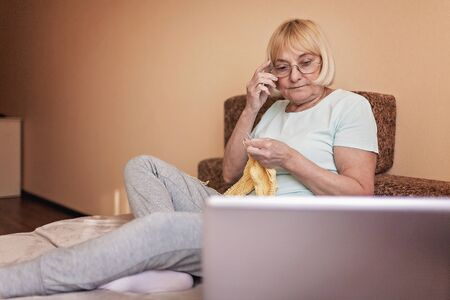 Concentrated old woman sitting on sofa, looking on the laptop screen and knitting a wool sweater at home during quarantine time, online hobby time, stay safe concept