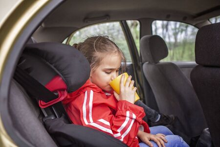 Child car safety, family travel. Pretty schoolchild sitting in car seat and holding a yellow cup, lunch during car journey, vacation after lockdown
