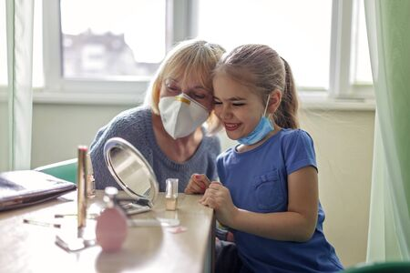 Multigenerational relations, care about seniors in new normal life, grandmother playing in beauty salon and helping grandkid to do makeup, they are wearing in medical respirators, social distance rule
