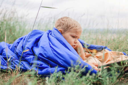 Local vacation. Cute boy having rest and dreaming alone in sleeping bag on the top of the mountain not far from village during local vacation, family summer weekend, social distance lifestyle