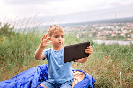 Local vacation. Cute boy having rest in sleeping bag on the top of the mountain not far from town and chatting with friends via internet, outdoor summer weekend, social distance lifestyle Banque d'images
