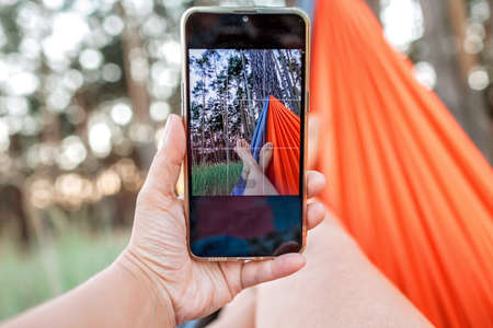 Local vacation. Woman having rest in hammock in the forest and making selfie for social network, local vacation, summer weekend, social distance lifestyle Banque d'images
