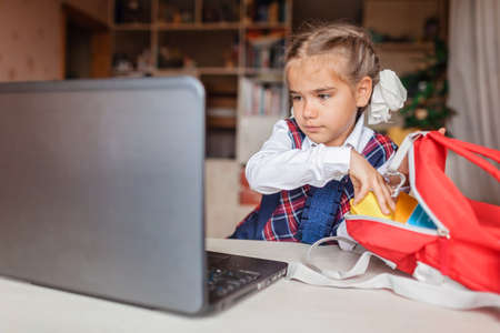 Back to school, new normal education. Cute girl in school uniform greeting somebody via video call and showing her new backpack. Social distance learning and new guidance Stock fotó