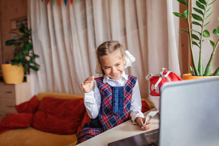 Back to school, new normal education. Cute girl in school uniform greeting somebody via video call and showing her new backpack. Social distance learning and new guidance 写真素材