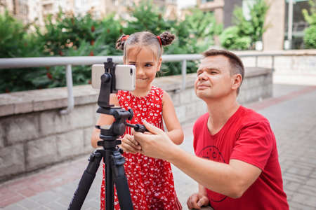 Make money online. Middle aged father and his daughter reviewing recorded film for family channel, video blogger, internet earning and freelance remote work Imagens