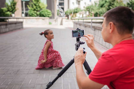 Make money online. Middle aged father and his daughter reviewing recorded film for family channel, video blogger, internet earning and freelance remote work