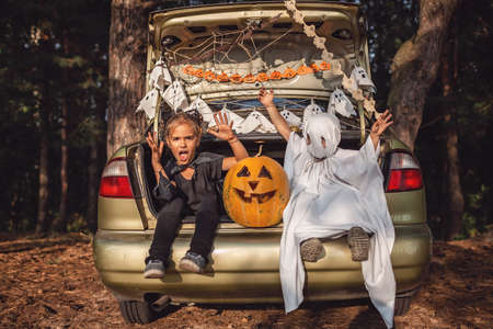 Alternative safe celebration. Cute kids preparing Halloween party in the trunk of car with carved pumpkin, spider net, ghosts and other decoration for Halloween, autumn outdoor.