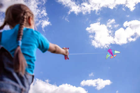 Happy childhood and summertime. Cute girl with yellow flowers in her hair having fun and playing with a kite on the meadow, blue sky and beautiful landscape. Summer outdoor, cope space background