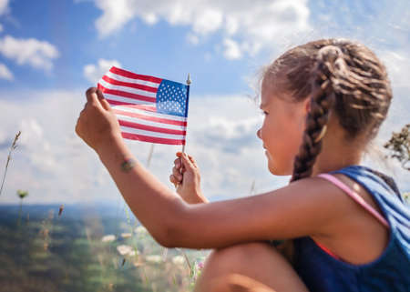 Patriot and National Flag day celebration. Cute little patriot sitting on the meadow and holding the national flag of United States over blue sky background, summer outdoor, soft focus on flag Stockfoto