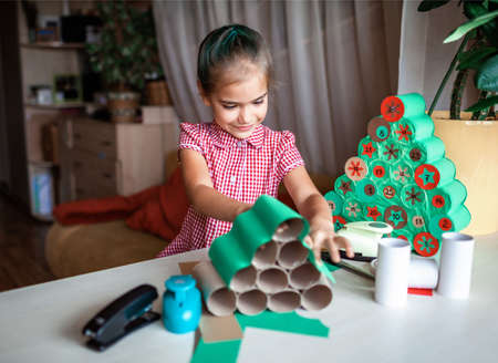 Cute little kid making handmade advent calendar with toilet paper rolls at home. Glue, colored paper, cut punch to hide sweets and candies in rolls. Seasonal activity for kids, family winter holidays