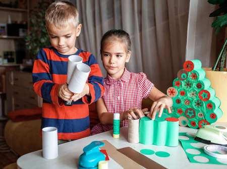 Cute little kids making handmade advent calendar with toilet paper rolls at home. Glue, colored paper, cut punch to hide sweets and candies in rolls. Seasonal activity for kids, family winter holidays