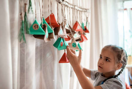 Cute little kid opening handmade advent calendar with color paper triangles. Sweets and candies are hidden in colorful triangles hanging on branch. Seasonal activity for kids, family winter holidays Stock Photo