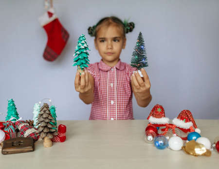 DIY decoration. Cute girl making a choice between common wrapped box with plastic bow and homemade wrapping with natural materials, pine needles, brunches and citrus slices, zero waste holidays