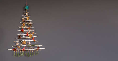 Original alternative Christmas tree made with frozen branches and decorated with tiny ecological toys and paper garland, zero waste holidays, isolated over gray background, copy space