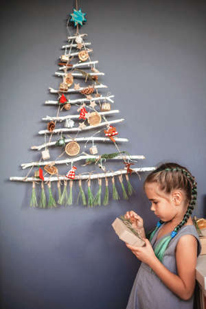 Happy girl having fun near original alternative Christmas tree made with frozen branches and decorated with tiny ecological toys and paper garland, zero waste and plastic free holidays Stock Photo
