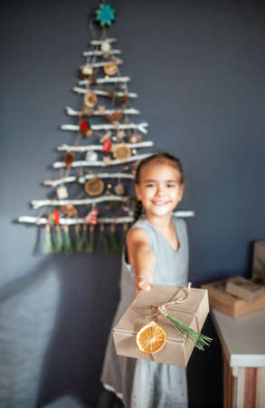 Happy girl holding out present box near original alternative Christmas tree made with frozen branches and decorated with tiny ecological toys and paper garland, zero waste and plastic free holidays