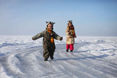 Happy two kid, brother and sister, walking on the frozen lake, having fun together, playing at winter walk outdoors, winter family lifestyle 免版税图像