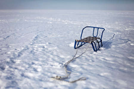 A child sledge staying on the snow in the middle of the frozen lake, happy wintertime, winter family lifestyle