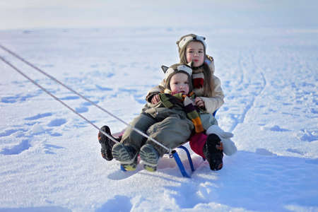 Smiling preschool girl in funny hat and warm coat and her little brother flying on a swing against the white field at winter walk outdoors, winter family lifestyle 免版税图像