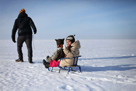 Happy family having fun, playing at winter walk outdoors, two kids and father, winter family lifestyle